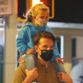Bradley Cooper and his daughter Leah walk through the night city
